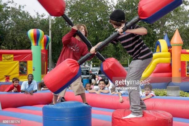 Two boys using pummel sticks in the combat area in the inflatable carnival games at the Family Street Party at Miami Science Museum