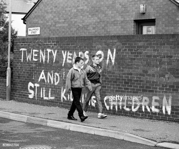 Two boys walk past the wall with the painted slogan 'Twenty years on and still killing our children' on Ballymoney Street in Belfast Seamus Duffy the...