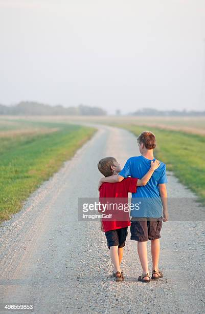 Two Boys Walking Down a Country Road