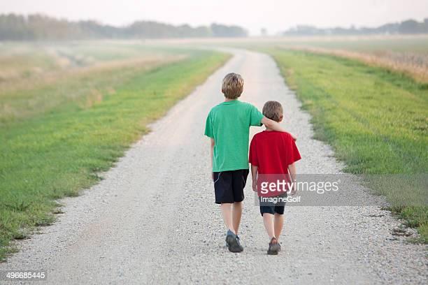 Deux garçons de marche sur une route de campagne