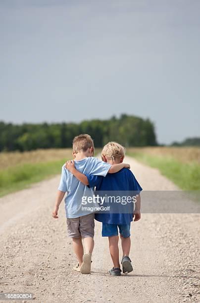 Deux garçons de marche sur une route de gravier
