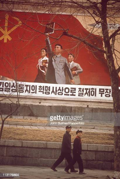Two boys walking past a poster depicting Communist revolutionaries North Korea February 1973