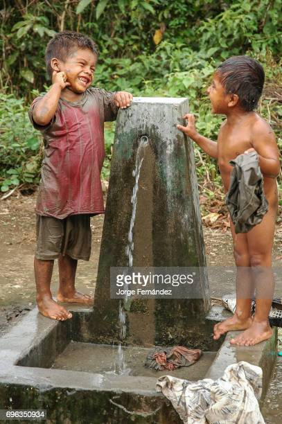 Two boys washing their clothes and having a bath in a drinking fountain