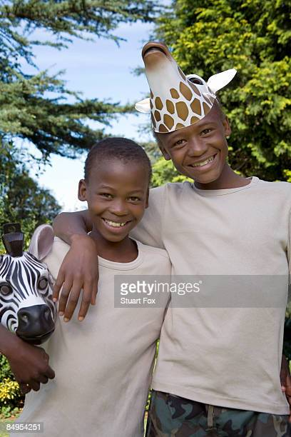 Two boys wearing animal masks stand side by side smiling, KwaZulu Natal Province, South Africa