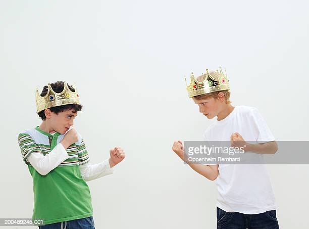 Two boys (7-9)wearing crowns facing each other, fists clenched