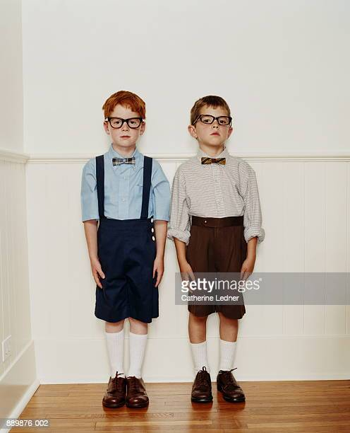Two boys (4-7) wearing glasses and bow ties, standing against wall