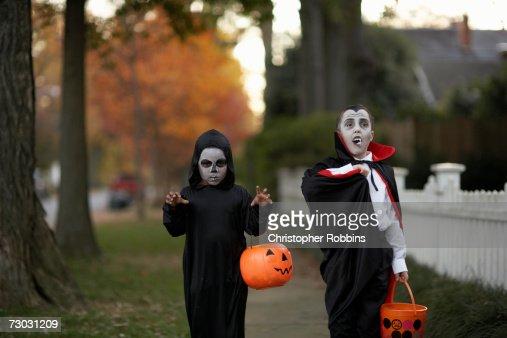 Two boys (6-7) wearing Halloween costumes walking on sidewalk : Stock Photo