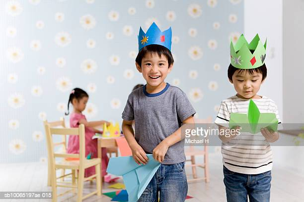 Two boys (4-5) wearing paper crowns, playing in room, portrait