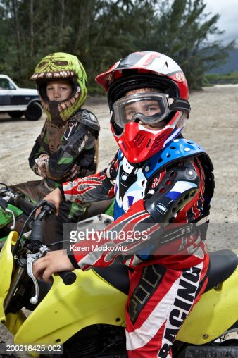 Two boys (9-12) wearing protective gear, sitting on dirt bikes : Stock Photo