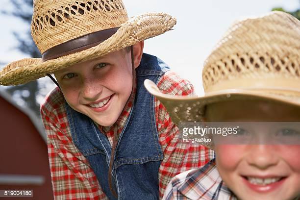 Two boys wearing straw hats