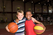 Two boys with basketballs in gym