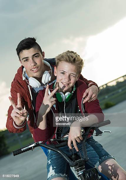 Two boys with BMX bike and headphones