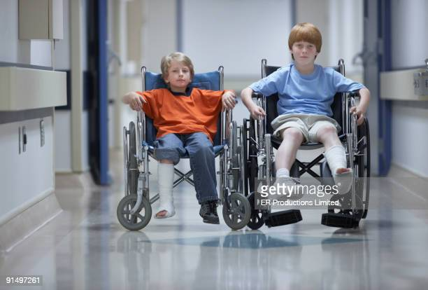 Two boys with casts in wheelchairs