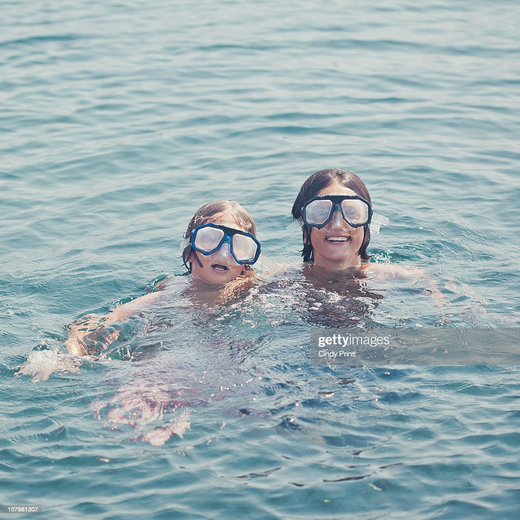 two boys with goggles swimming in the ocean stock photo
