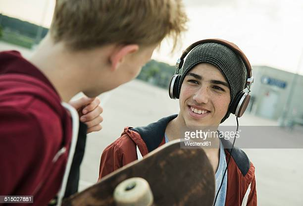 Two boys with headphones and skateboard