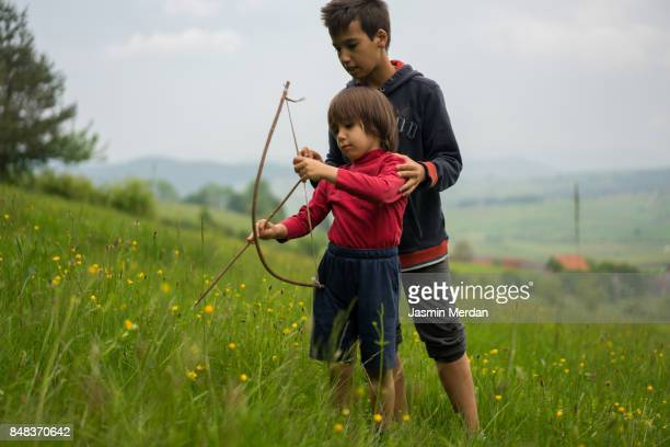 Two boys with homemade bow and arrow