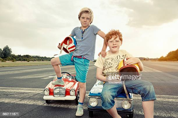 Two boys with pedal cars on race track