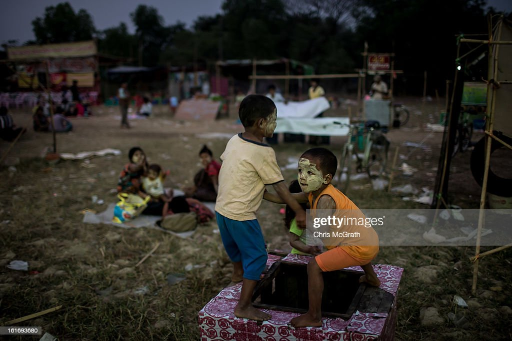 Two boys wrestle over a water hole amusement stand at a rural carnival in South Dagon Township on February 14, 2013 in Yangon, Burma. Myanmar is going through rapid political and economic reforms initiated by the countries first civilian president Thein Sein after years of military junta rule.
