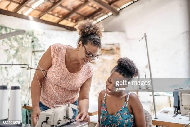zwei Brasilianerin an Nähmaschine in Schneider Arbeitsraum von Sozialprojekt