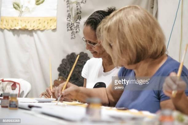 zwei brasilianische Frau Malerei Textilien im Arbeitszimmer des Sozialprojekt