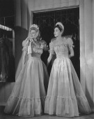 Two bridesmaids in dresses made of silk mousseline with a soft full bodice with ruffled edge outlining the square neck short puff sleeves and a deep...