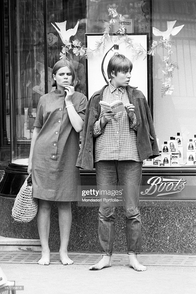 Two British girls waiting barefoot in front of a shop window. London, 1960s