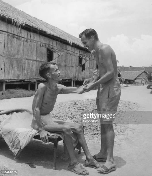 Two British inmates of the Changi prisonerofwar camp on Singapore after the island's liberation from Japanese occupation following World War II...