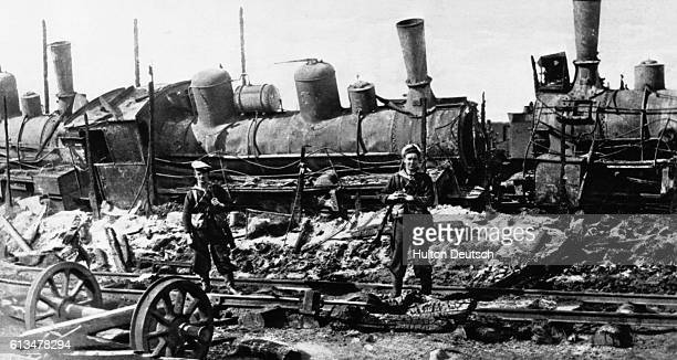 Two British Navy sailors stand guard over a pair of steam locomotives damaged by the Bolsheviks at the advanced base of Saroka on the Murmansk front