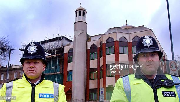 Two British police officers stand outside the Finsbury Park Mosque after police conducted a raid in the early morning hours resulting in the arrest...