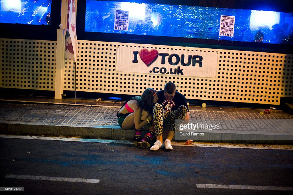 Two British students sit on the pavement outside a nightclub during the first night of parties during the SalouFest on April 1, 2012 in Salou, Spain. Saloufest is a sporting tour event where thousands of British university students take part in different sport competitions and join parties during the Easter holidays in the Catalan village of Salou.