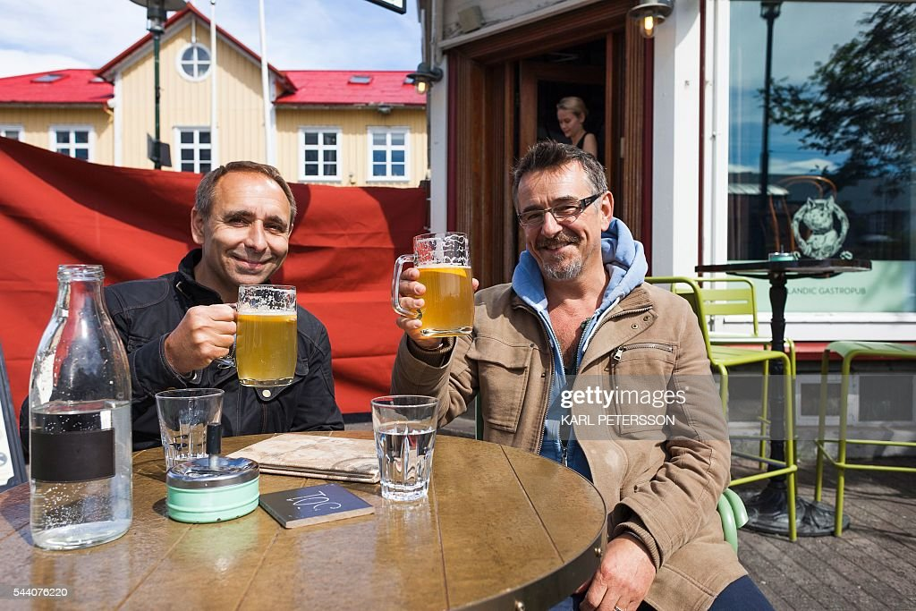 Two British tourists pose with a beer in Reykjavik, on July 1, 2016. With a large part of its population in France for the Euro 2016, Iceland has pretty much come to a standstill these days, except for its tourism sector which is booming. / AFP / Karl Petersson / TO