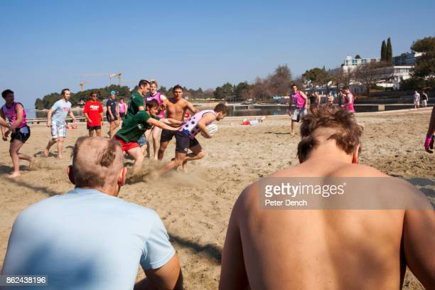 Two British university students with chunks shaved out of their hair watch rugby being played on the beach at the Zelena Laguna resort near Porec...