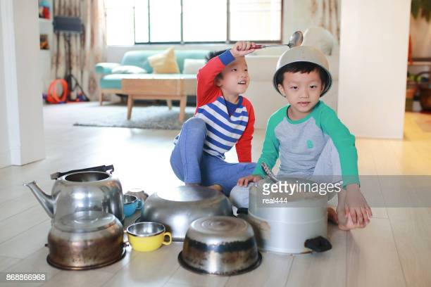 Two brother playing on floor with pots and pans