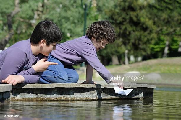 Zwei Bruder spielt mit Papier-Boote