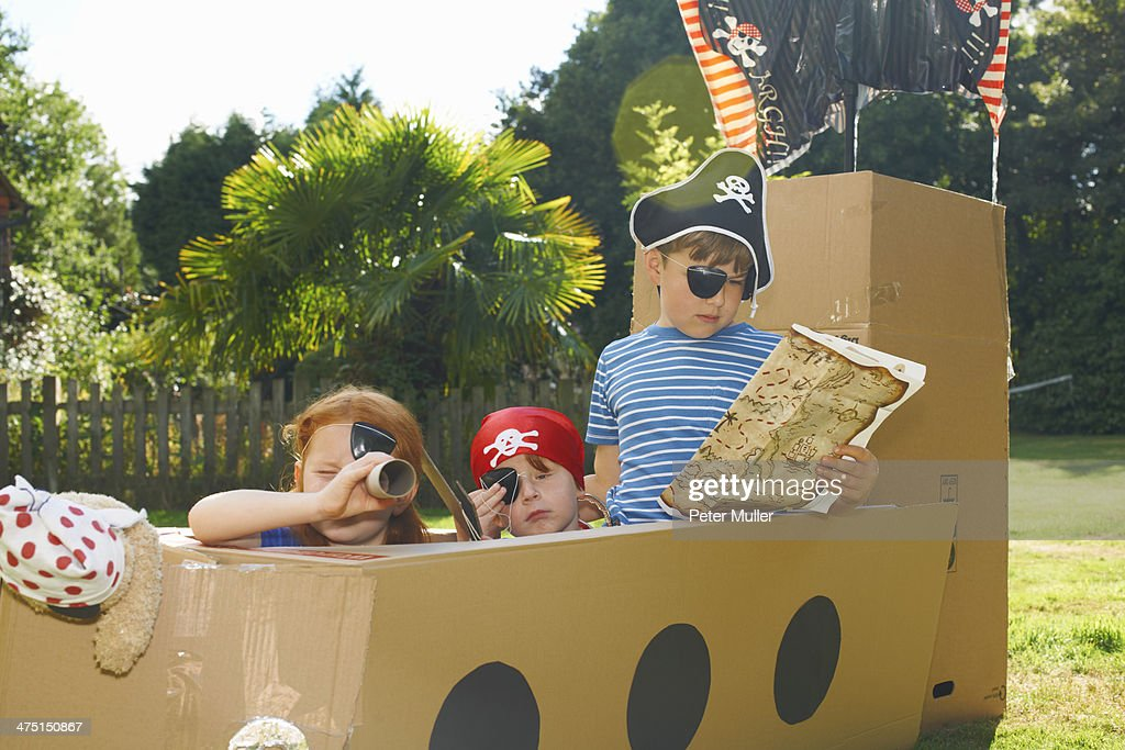 Two brothers and sister playing with homemade pirate ship in garden