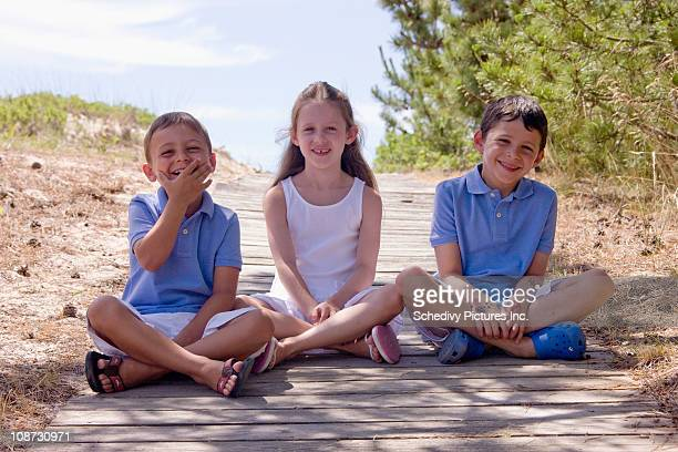Two brothers and sister sitting in shade at beach