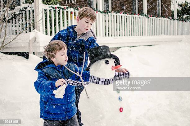 Two brothers building a snowman