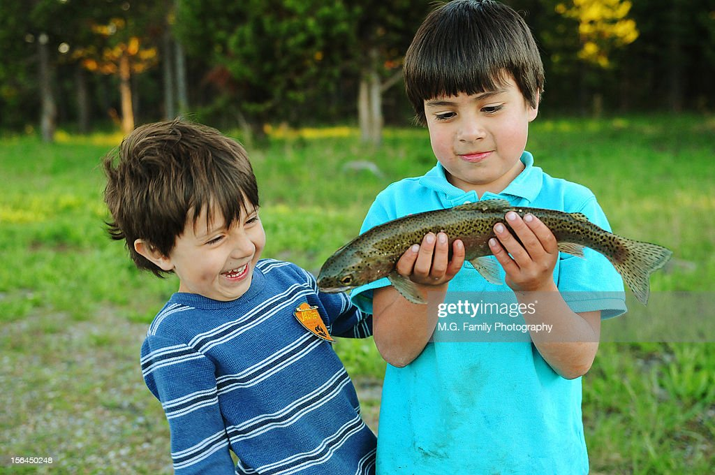 Two brothers examining the trout they caught : Stock Photo