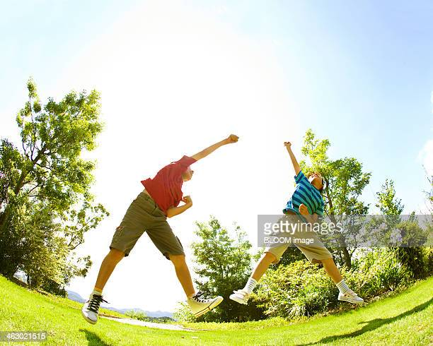 Two Brothers Jumping In Park