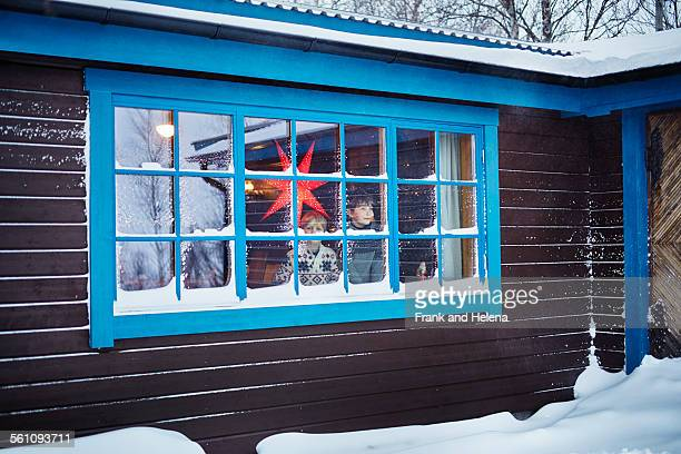 Two brothers looking out of snow covered cabin window at Christmas