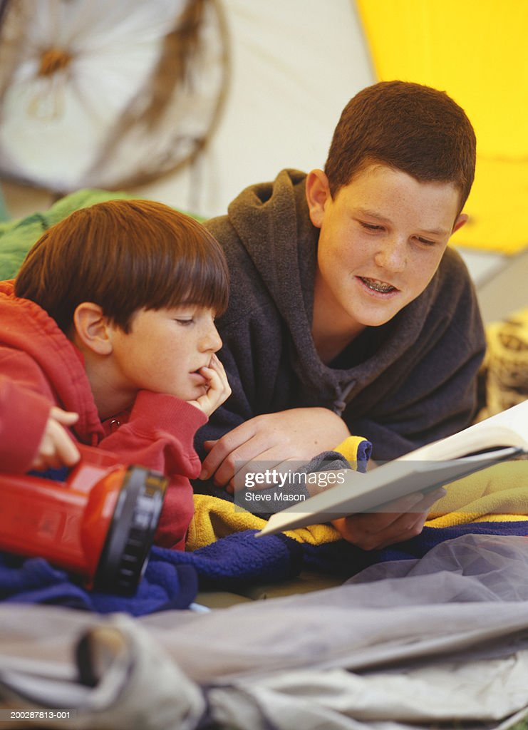 Two brothers (10-14) lying in tent, reading book : Stock Photo