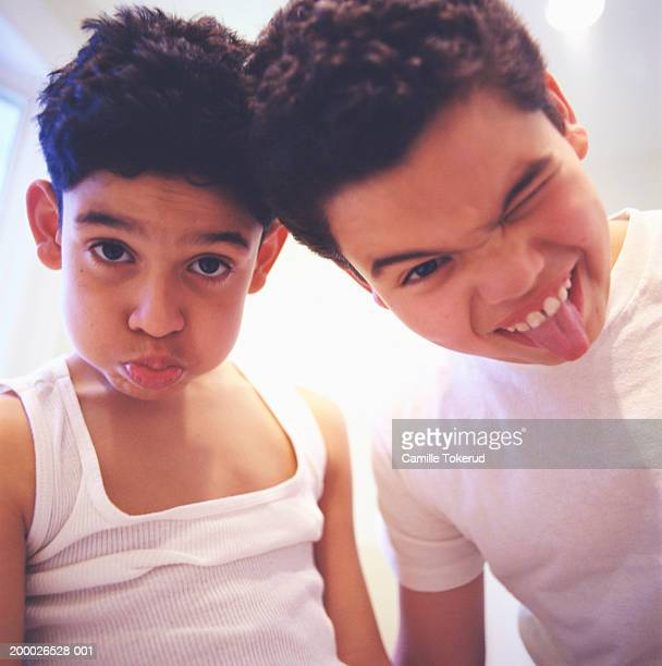 Two brothers (10-13) making faces, close-up