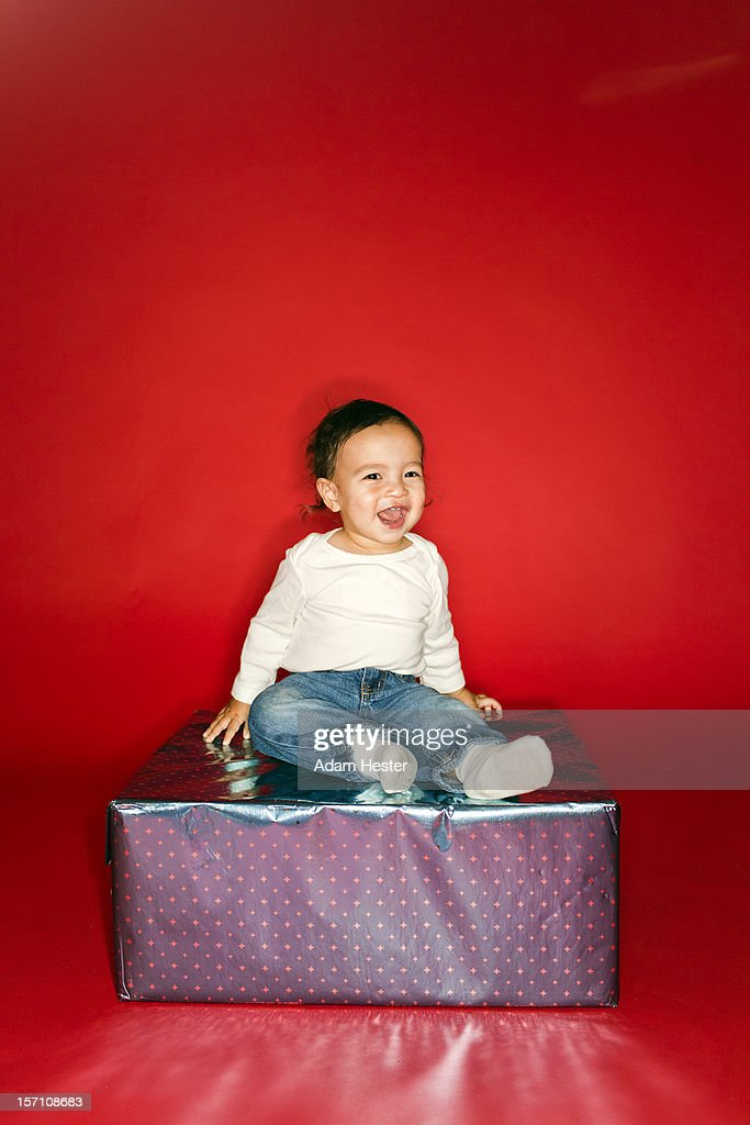 Two brothers on top of a present smiling. : Stock Photo