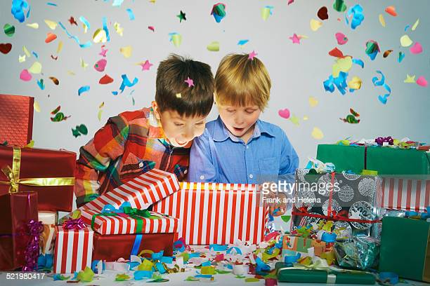 Two brothers open mouthed on unwrapping glowing christmas gift box with exploding confetti