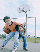 Two brothers (3-7) playing on basketball court, portrait