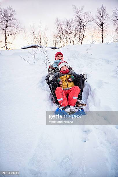 Two brothers playing on toboggan on snow covered hill, Hemavan,Sweden