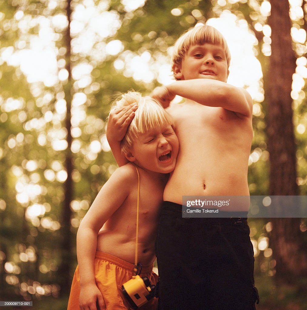 Two brothers (5-9) playing outdoors : Stock Photo
