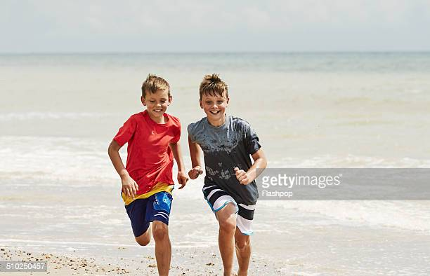 Two brothers running on the beach