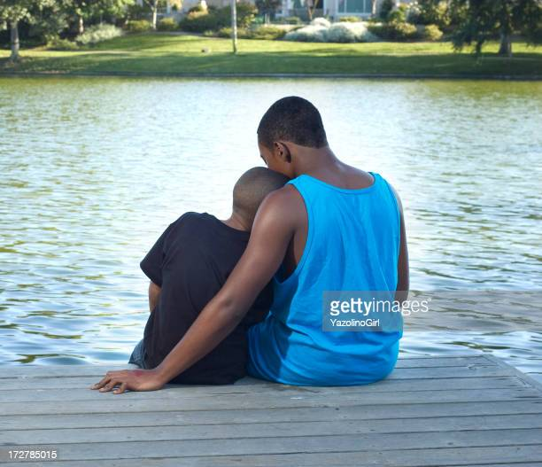 Two Brothers sitting near pond