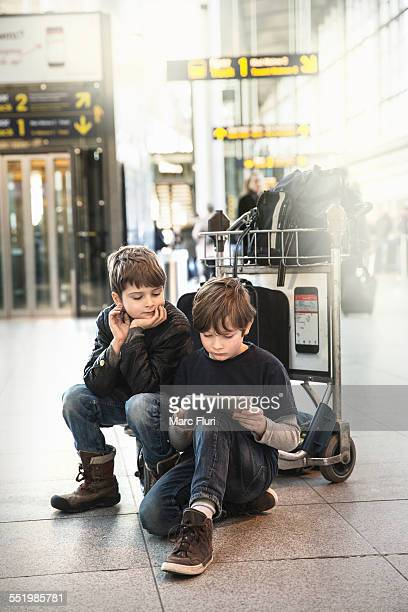 Two brothers sitting on airport luggage trolley looking at digital tablet